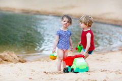 Little toddler friends having fun together on the beach Stock Photos