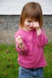 Little  toddler girl is ashamed. Shy or ashamed little toddler girl outside in the garden rubs through her eyes royalty free stock image
