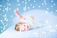 Little toddler girl in bed between sparkling blue lights Royalty Free Stock Images