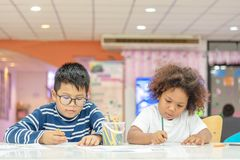 Little toddler girl and boy concentrate drawing together. Asian boy and Mix African girl learn and play together in the pre-. School class. Children enjoy hand royalty free stock photo