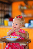 Little toddler girl eating breakfast in cafe Stock Images