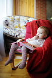 Little toddler girl eating chocolate. And reading a book Royalty Free Stock Images