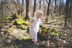 Little Toddler Girl Exploring Nature in the Woods. A two year old baby toddler girl is exploring nature, picking up sticks, moss, and dirt in the deciduous royalty free stock photography