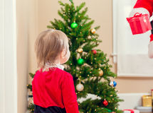 Little toddler girl getting a gift from Santa Claus Stock Image