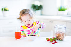 Little toddler girl having breakfast drinking juice Royalty Free Stock Image