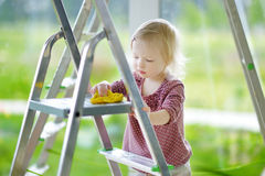 Little toddler girl helping her mom to clean up Royalty Free Stock Photography