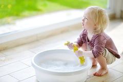 Little toddler girl helping her mom to clean up Stock Photo