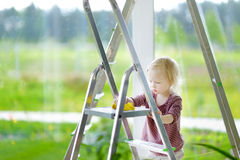 Little toddler girl helping her mom to clean up Stock Image