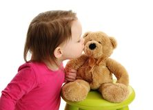Little toddler girl kissing a teddy bear. Young toddler preschool girl giving a kiss to a brown teddy bear Royalty Free Stock Image