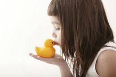 Little toddler girl kissing a yellow bath duck Stock Photography