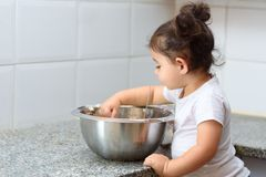 Little toddler girl kneading dough in kitchen. stock images