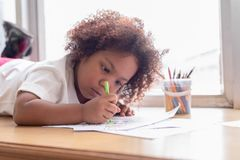 Little toddler girl laying down concentrate on drawing. Mix African girl learn and play in the pre-school class. Children enjoy. Hand writing. 3 years girl royalty free stock image