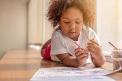Little toddler girl laying down concentrate on drawing. Mix African girl learn and play in the pre-school class. Children enjoy. Hand writing. 3 years girl stock photos