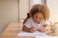 Little toddler girl laying down concentrate on drawing. Mix African girl learn and play in the pre-school class. Children enjoy. Hand writing. 3 years girl royalty free stock photos