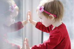Little toddler girl looking through a window Royalty Free Stock Images