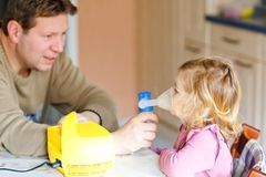 Little toddler girl making inhalation with nebulizer at home. Father helping and holding the device. Child having flu stock photo