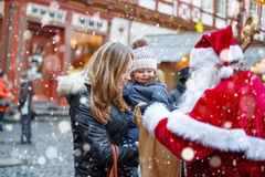 Little toddler girl with mother on Christmas market. Royalty Free Stock Images