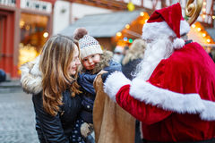 Little toddler girl with mother on Christmas market. Stock Images