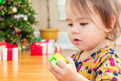 Little toddler girl playing with her toys in front of the Christmas tree Royalty Free Stock Images