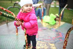 Little Toddler Girl Playing on Merry-Go-Round at Playground. A 1 year old little toddler girl is playing happily with her friends at a playground on a merry go Stock Image
