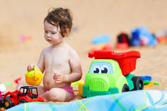 Little toddler girl playing with sand toys on the beach Royalty Free Stock Image
