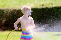 Little toddler girl playing with water hose in the garden Stock Image