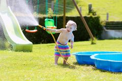 Little toddler girl playing with water hose in the garden. Happy little child, funny blonde toddler girl playing with water hose outdoors in the garden at the stock photography