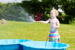 Little toddler girl playing with water hose in the garden Stock Images