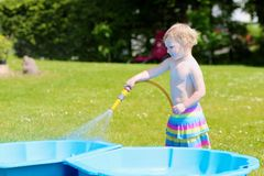 Little toddler girl playing with water hose in the garden royalty free stock images