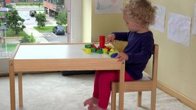 Little toddler girl playing with wooden bricks toys near table at home stock video