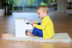 Little toddler girl plays toy piano stock photo