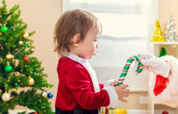 Little toddler girl receiving a candy cane from Santa Claus Royalty Free Stock Image