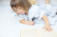 Little toddler girl refusing to read book. And to learn looking unhappy Royalty Free Stock Photo