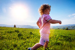 Little toddler girl running in a beautiful field Stock Photos