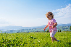 Little toddler girl running in a beautiful field Stock Image