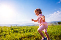 Little toddler girl running in a beautiful field Royalty Free Stock Photo