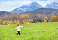 Little toddler girl running in a beautiful field between snow co Royalty Free Stock Image