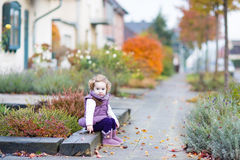 Little toddler girl sitting on front yard of house. Little toddler girl with curly hair sitting on the front yard of a beautiful house in a small European Royalty Free Stock Image