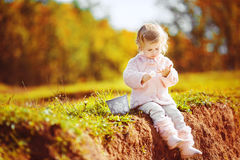 Little toddler girl sitting in green summer park Royalty Free Stock Image