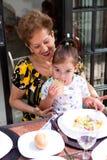 Little toddler girl sitting on her grandmot Royalty Free Stock Images