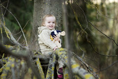 Little toddler girl sitting at a tree branch Royalty Free Stock Photos