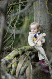 Little toddler girl sitting at a tree branch Royalty Free Stock Photo