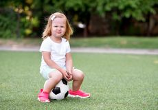 Little toddler girl in sports uniform and pink sneakers sitting on a soccer ball in a green football field outdoors with a funny royalty free stock photos