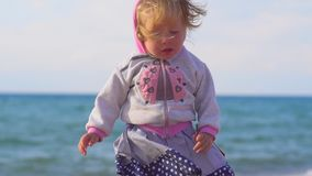 The child stands by the sea. Little toddler girl standing in the sand of the beach alone looking at the sea on a Sunny summer day stock video