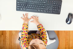 Little toddler girl using her computer from above Stock Image