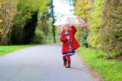 Little toddler girl walking with umbrella Stock Photo