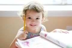 Little toddler girl writing at school desk royalty free stock images