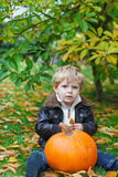 Little toddler with green pumpkin in garden Royalty Free Stock Image