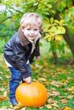 Little toddler kid boy with big pumpkin in garden Royalty Free Stock Photos