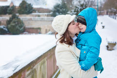 Little toddler kid boy and mother having fun with snow on winter day Stock Photos